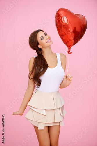 Vivacious sexy woman with heart balloon