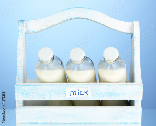Milk in bottles in wooden box on blue background