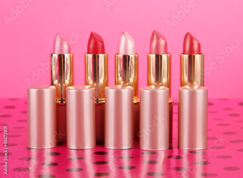 Lipsticks on table on pink background