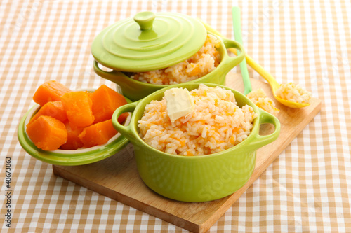 Taste rice porridge with pumpkin in saucepans