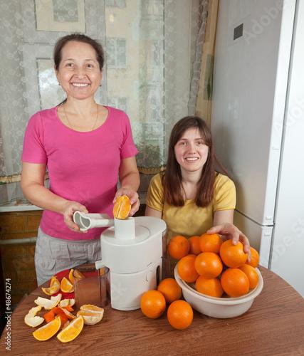 Two women  making fresh orange juice