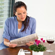 Woman reading newspaper relaxing wine living room