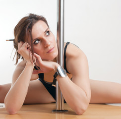 The young beautiful woman is engaged at a pole
