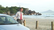 Businessman talking on cell phone beside his car on a beach