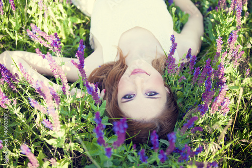 Girl liyng on spring grass and flowers.