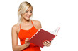Smiling woman in red dress reading a book