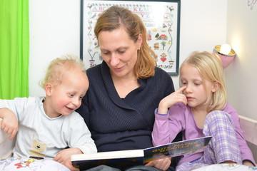 Mutter ließt Kindern im Bett eine Geschichte vor