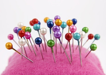 Multicolored sewing pins in pin cushion close up