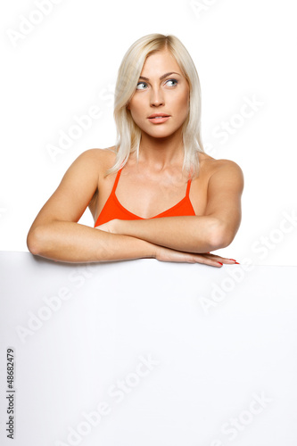 Woman leaning on white billboard looking to side