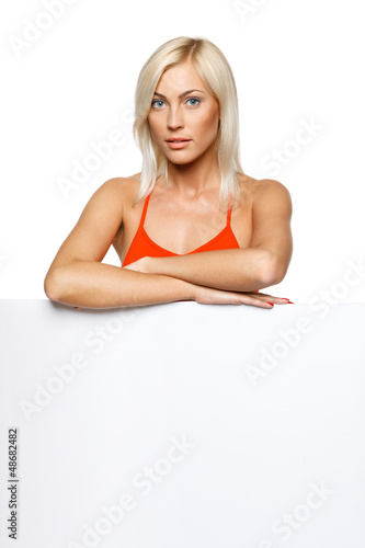 Calm woman standing behind and leaning on white billboard