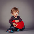Little kid with red heart. Studio shot.