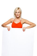 Smiling woman standing behind and holding white blank billboard