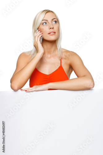 Concentrated woman leaning on whiteboard talking on cellphone