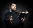 Priest with Prayer book against dark background