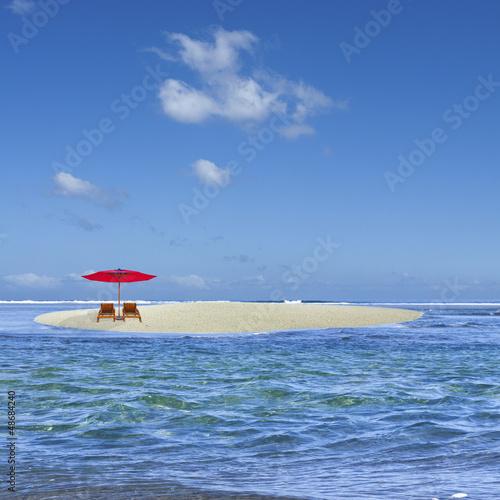 parasol rouge sur îlot de sable blanc