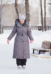 Beautiful woman in winter coat is skating