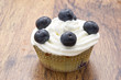 Chocolate muffins with blueberries and white cream