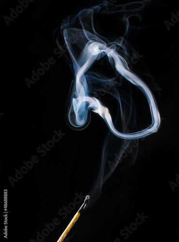 Fireless match and circle of smoke on black background