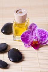 botella de fragancia con flor y piedras