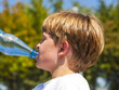 young boy drinks water out of a bottle