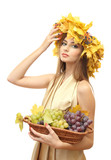 beautiful young woman with yellow autumn wreath and grapes in