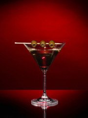 Martini glass and olives on dark background