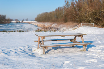 Freshly fallen snow on a wooden picnic table and bench
