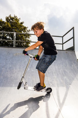 boy enjoys jumping with his scooter in the halfpipe