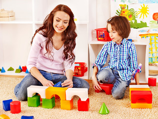 Family with child playing bricks.