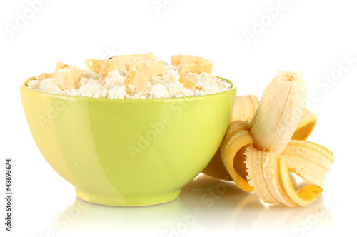 Cottage cheese in color bowl with banana, isolated on white