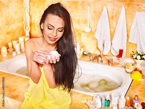 Woman applying moisturizer.
