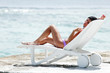Woman in chaise-lounge near sea