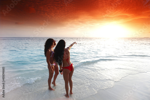 Two women enjoying sunset on beach