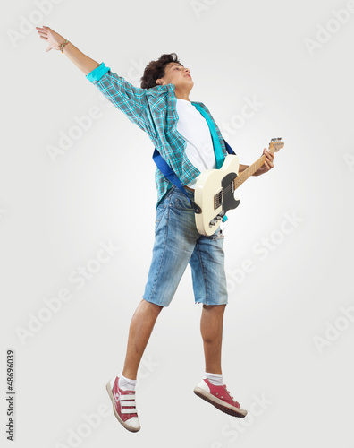 young man playing on electro guitar and jumping