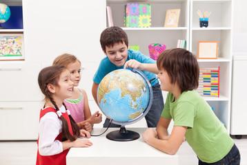 Kids looking at earth globe