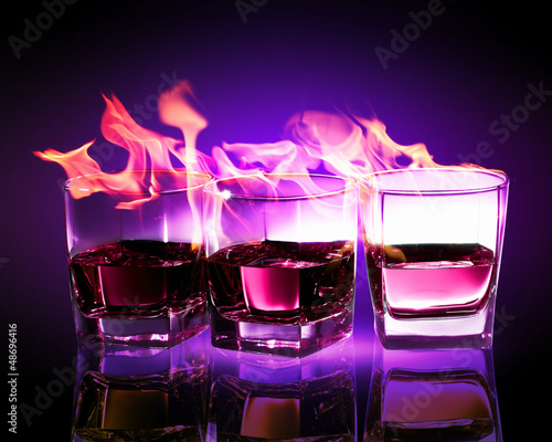Three glasses of burning purple absinthe