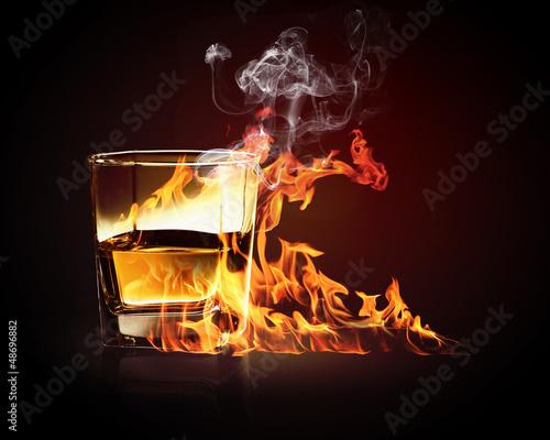 Glass of burning yellow absinthe