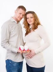 mann mit schwangerer frau und babyschuhe