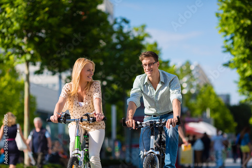 Couple - man and woman - riding bikes or bicycles