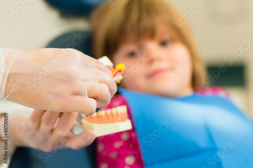 Dentist with toothbrush, denture, and little patient