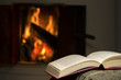 Peaceful and warm image of a open book by fireplace.