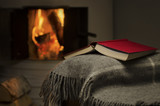 Fototapety Peaceful and warm image of a open book by fireplace.