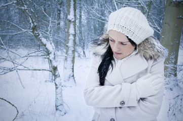 woman alone and cold in forest covered by snow