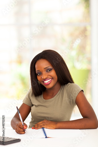 pretty african american college student studying at home