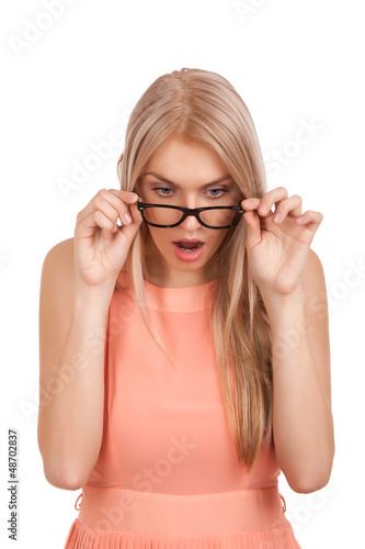 Surprised blond woman looking down over glasses