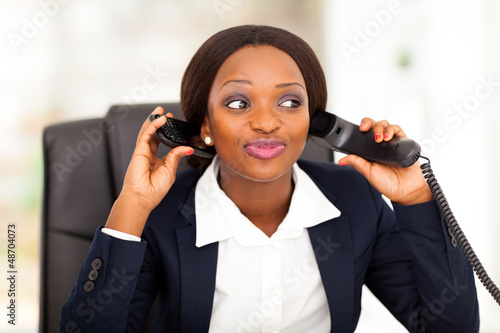 female african american office worker talking on two phones