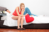 Disappointed female with heart sitting on a bed while her boyfri