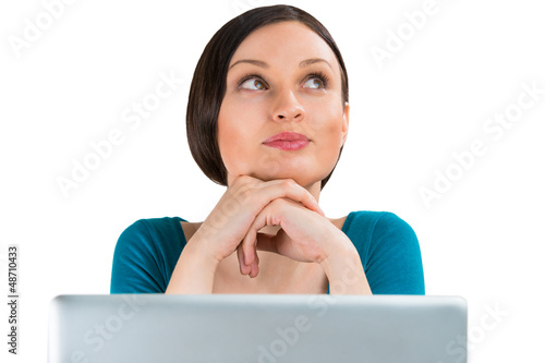 Young pretty woman sitting in front of laptop and thinking about