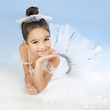 Little ballerina in white dress over blue