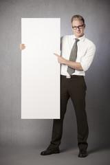 Smiling businessman presenting white blank billboard.